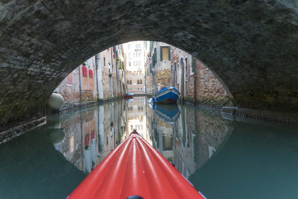 with the kayak paddling under a small bridge in Venice